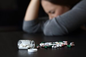 Depressed woman beside a lot of pill