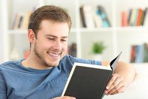 Happy guy reading a paper book
