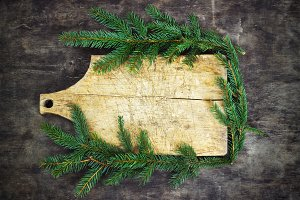 Old cutting board with spruce branches on a wooden background kitchen cooking christmas