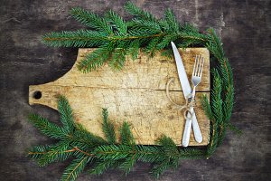 Old cutting board with spruce branches on a wooden background with fork and knife kitchen cooking christmas