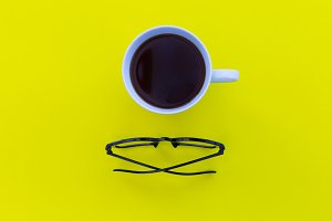 Coffee + eyeglasses on yellow