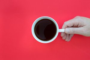 Hand holding coffee on red