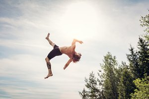 Young man doing a backflip in the air.