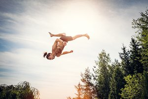 Young man jumping high in the sky.