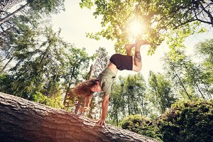 Young man doing a handstand on a tree trunk in the forest.