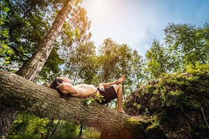Young man lying and relaxing in the forest.