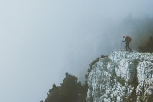 Traveler on foggy cliff mountains