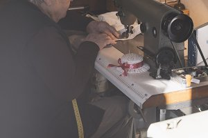 The old woman sews on the sewing mac