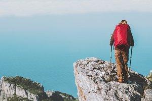 Tourist on rocky cliff mountains