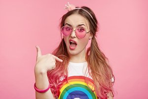 Indignant fashionable female model indicates at herself, has unpleasant look, asks why she should do everything alone. Headshot of stylish woman in pink glasses and bracelet points or chooses