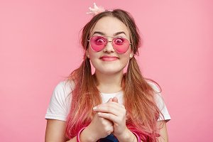 Pretty fashionable female with pink hair, keeps hands together, looks happily with intriguing expression as going to recieve present from boyfriend, isolated over pink background. Unexpectedness