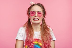 Sorrorful crying pin up girl wears pink glasses, being in despair as has no money for buying new clothes. Grieved glamour pretty woman with two pony tails has troubles in life, looks desperate