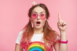 Surprised stylish young female with pink hair, spectacles, bracelet, raises fore finger as understands something, gets idea, poses indoors over blank copy space. Fashionable glamour woman. Fashion