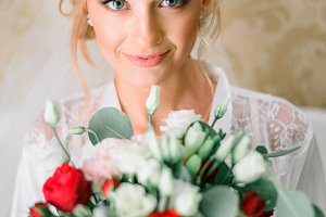 Blonde bride with red bouquet