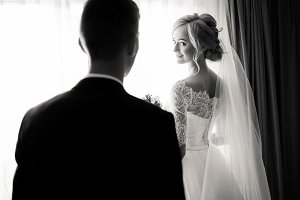 Charming couple stands near window