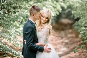 Handsome young groom kisses bride