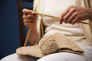 Cropped image of old woman knitting.