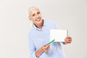 Smiling mature woman showing notebook with copy space for text isolated