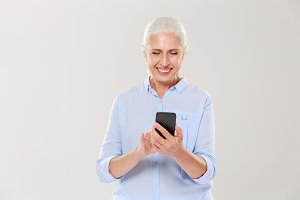 Mature smiling woman using smartphone isolated