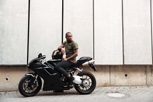 Portrait of a young afro american man on a motorcycle