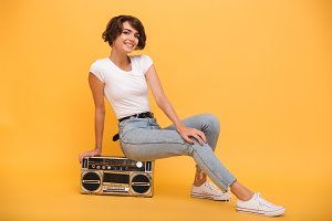 Portrait of a joyful young girl sitting record player