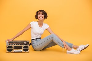 Portrait of a pretty joyful girl sitting with record player