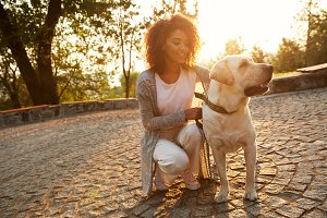 Young smiling lady in casual clothes sitting and hugging dog in park