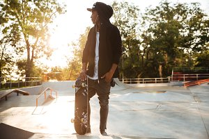 Young african man skateboarder standing