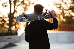 Back view of a male teenager guy holding skateboard