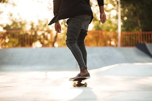 Cropped image of a young teenage skateboarder in action