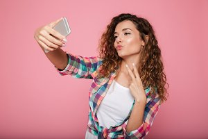 Young beautiful woman making selfie on smartphone isolated