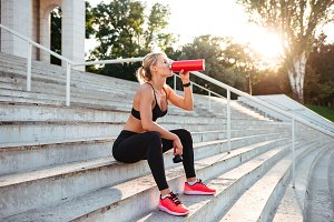 Beautiful strong young sports woman drinking water