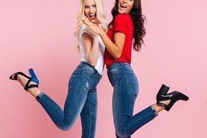 Vertical image of two cheerful women posing in studio
