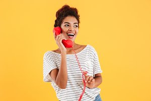 Cheerful lady talking on red telephone and looking aside