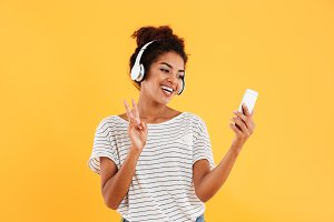 Cheerful positive young woman in headphones using smartphone isolated