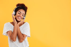 Young beautiful lady with curly hair listening music isolated