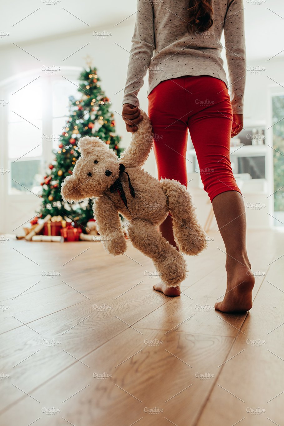 74b4f51e9d Little girl with her Christmas gift. - Holidays. Low section of young girl holding  teddy bear walking towards Christmas tree.