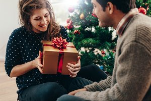 Young couple exchanging Christmas