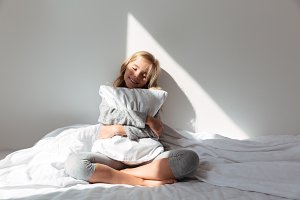 Portrait of a smiling little girl hugging pillow
