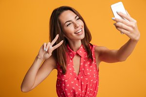 Smiling brunette woman in dress making selfie on smartphone