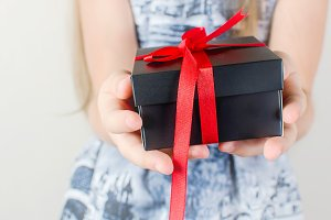 Little girl holding black gift box