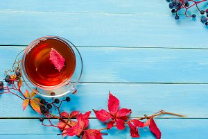 Hot tea on yellow autumn leaves