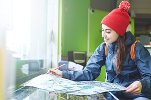 woman traveler sitting at a table looking at map