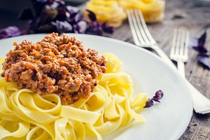 Pasta with bolognese sauce on wooden background
