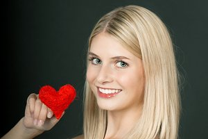 Young blond girl with red heart