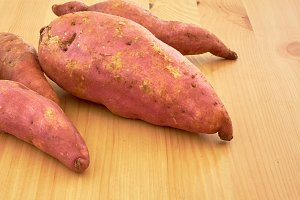 Sweet potatoes on a rustic wooden table
