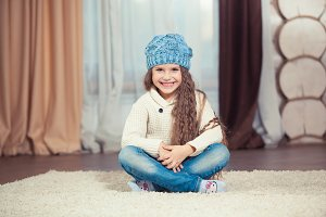 Little girl in a sweater and hat sits on the floor in a wooden house, christmas.