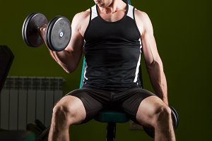 Muscular man working out in gym doing exercises with dumbbells, bodybuilder male naked torso