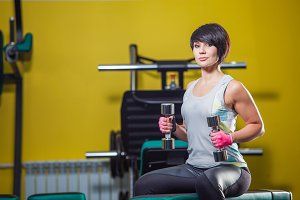 Image of muscle woman doing exercises in gym.