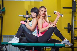 Two young sporty woman in the gym centre.